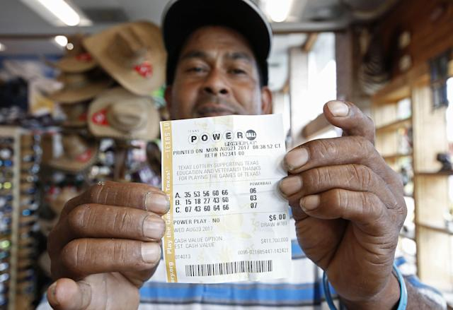 <p>A man holds up a Powerball lottery ticket he purchased at a gas station in Dallas, Texas, Aug. 23, 2017. The Powerball is at 700 million US dollars (593 million euro). (Photo: Larry W. Smith/EPA-EFE/REX/Shutterstock) </p>