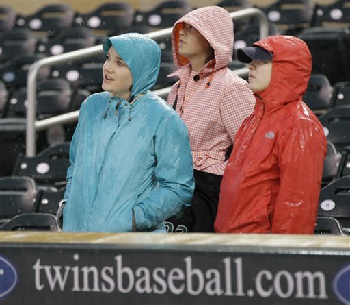 Baseball fans brave a rain delay which held up the Minnesota Twins and Toronto Blue Jays baseball game on Friday, May 11, 2012, in Minneapolis. (AP Photo/Jim Mone)