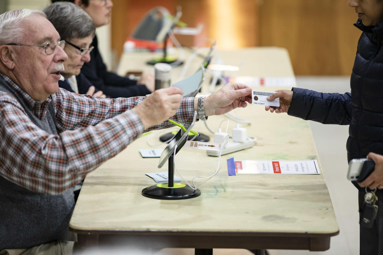 An election official hands a voter back their ID at the Madison Community Center polling place before he can cast his ballot in the Democratic presidential primary on Super Tuesday on March 3, 2020 in Arlington, VA. (Samuel Corum/Getty Images)
