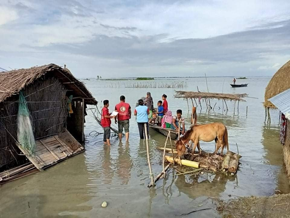 In this photograph provided by International Federation of Red Cross and Red Crescent Societies (IFRC) shows IFRC volunteers reaching flood affected communities with drinking water and other support in Kurigram, Bangladesh, July 16, 2020. More than 9.6 million people across South Asia have been affected by severe floods, with hundreds of thousands struggling to get food and medicine, officials and aid organizations said Wednesday. (IFRC via AP)