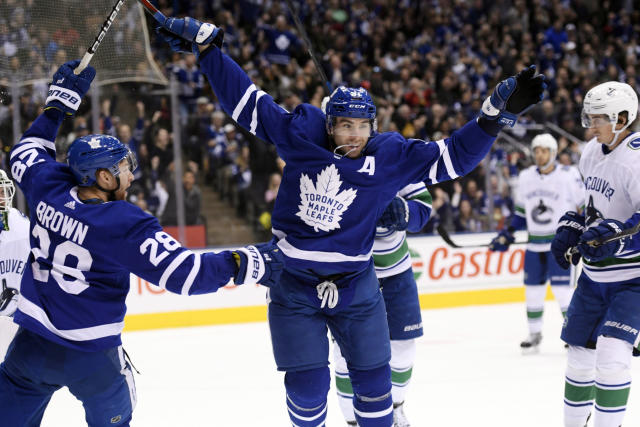 Toronto Maple Leafs center John Tavares (91) celebrates his goal against the Vancouver Canucks with teammate Connor Brown (28) during the first period of an NHL hockey game, Saturday, Jan. 5, 2019, in Toronto. (Nathan Denette/The Canadian Press via AP)