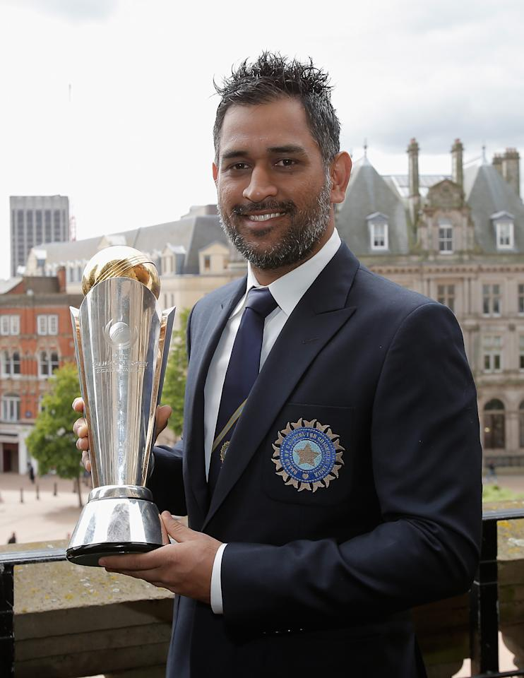 BIRMINGHAM, ENGLAND - JUNE 24: Indian captain MS Dhoni poses with the Champions Tophy during a photocall for the winners of the ICC Champions Trophy on June 24, 2013 in Birmingham, England.  (Photo by Harry Engels-ICC/ICC via Getty Images)