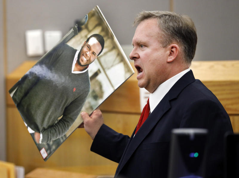 Assistant District Attorney Jason Hermus waves a photo of Botham Jean at the jury as he presents his closing arguments in Amber Guyger's murder trial in the 204th District Court at the Frank Crowley Courts Building in Dallas, Monday, September 30, 2019.  Guyger shot and killed Botham Jean, an unarmed 26-year-old neighbor in his own apartment last year. She told police she thought his apartment was her own and that he was an intruder. (Tom Fox/The Dallas Morning News via AP, Pool)