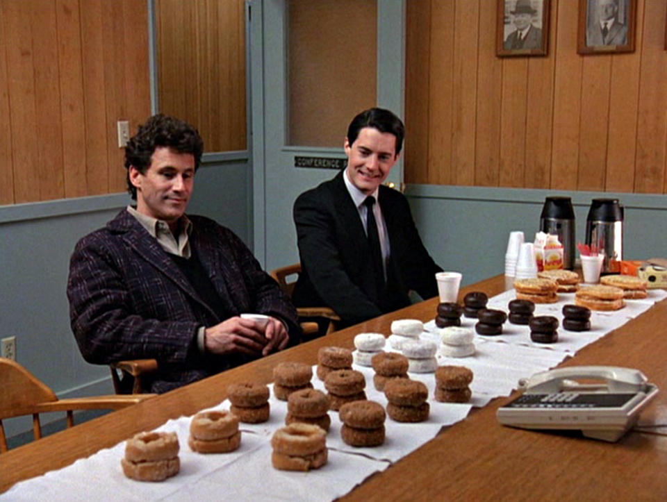 Michael Ontkean as Sheriff Harry S. Truman (left) and Kyle MacLachlan as Special Agent Dale Cooper eye donuts arrayed on a table in a scene from the pilot episode of 'Twin Peaks'. (Photo by CBS Photo Archive/Getty Images)