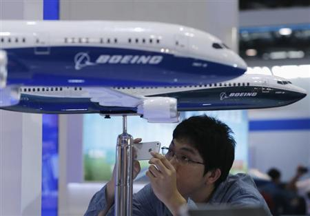 A visitor takes a picture of miniature Boeing passenger aircraft on display at Aviation Expo China 2013 in Beijing