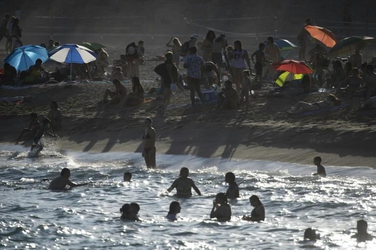 People enjoy a day at El Bogatell Beach in Barcelona on July 1, 2020, as European countries reopen their borders to some nations (AFP Photo/Josep LAGO)