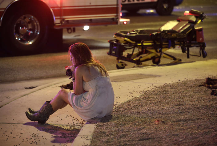 <p>A woman sits on a curb at the scene of a shooting outside of a music festival along the Las Vegas Strip, Oct. 2, 2017, in Las Vegas. Multiple victims were being transported to hospitals after a shooting late Sunday at a music festival on the Las Vegas Strip. (Photo: John Locher/AP) </p>