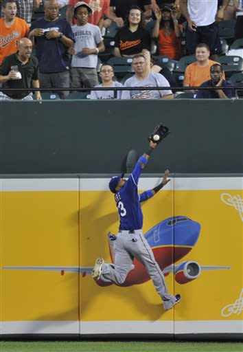 Texas Rangers centerfielder Engel Beltre reaches a fly ball hit by Baltimore Orioles' Brian Roberts but is unable to catch it in the fourth inning of a baseball game on Wednesday, July 10, 2013, in Baltimore. Roberts drove in a run on the single.(AP Photo/Gail Burton)