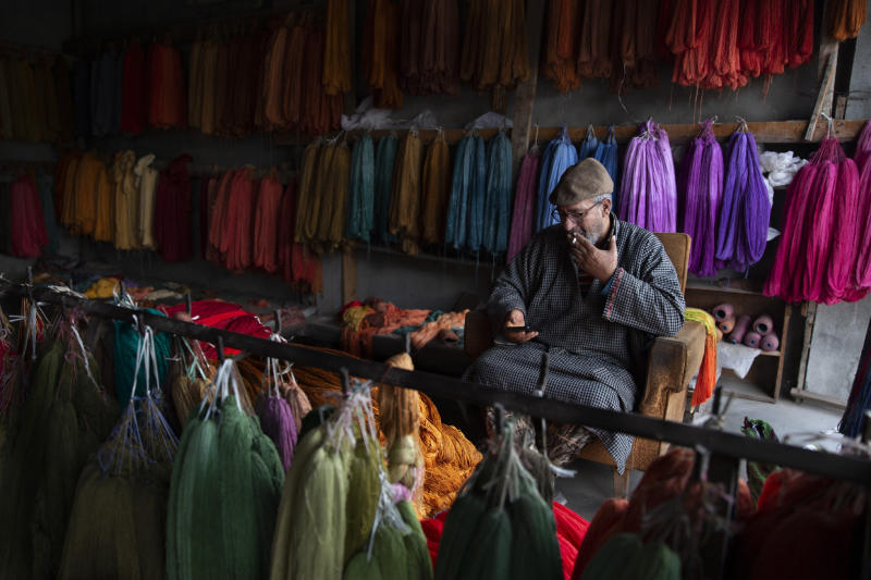 In this Jan. 30, 2020, photo,Kashmiri shopkeeper Mohammad Ashraf browses the internet on his mobile phone in  Srinagar, Indian controlled Kashmir. Six months after India stripped restive Kashmir of its semi-autonomy, enforcing a total communications blackout, it has restored limited internet at slow speeds with access only to government-approved websites. Since Modi came into power in 2014, the internet has been suspended more than 365 times in India, according to the global digital rights group Access Now. (AP Photo/ Dar Yasin)