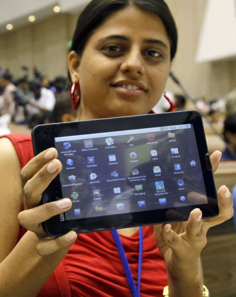 "An Indian student poses with the supercheap 'Aakash' Tablet computer which she received during its launch in New Delhi, India, Wednesday, Oct. 5, 2011. The $35 basic touchscreen tablet aimed at students can be used for functions like word processing, web browsing and video conferencing. 'Aakash' , manufactured by DataWind has a 7""Android 2.2 touch screen and a HD video co- processor. The Indian government intends to deliver 10 million tablets to students across India. (AP Photo/Gurinder Osan)"