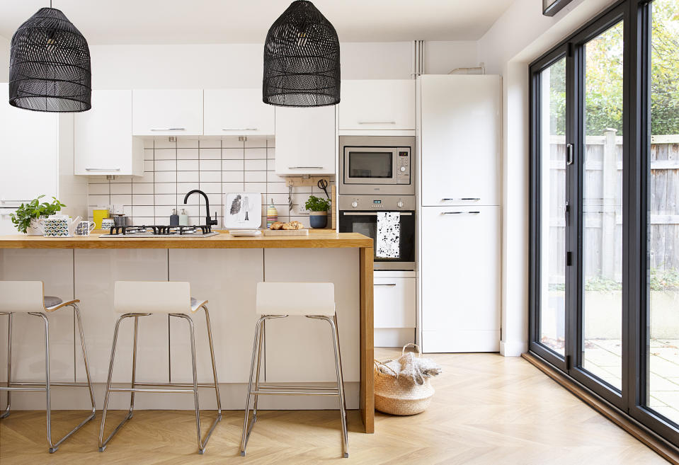Kitchen in the open-plan kitchen-diner with white units and wall hung cabinets, an island with wrap-around wooden worktop, white bar stools and black mesh pendant lights