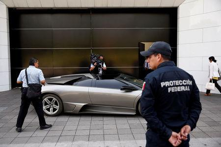 A police officer stands near a Lamborghini Murcielago 2007, part of the fleet of vehicles seized by the government from politicians and organized crime as part of an auction in Mexico City