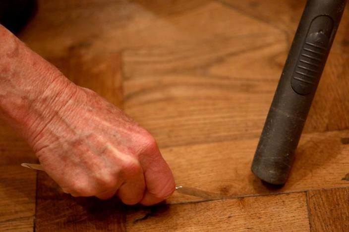 Close-up of hands using a small spatula and vacuum.