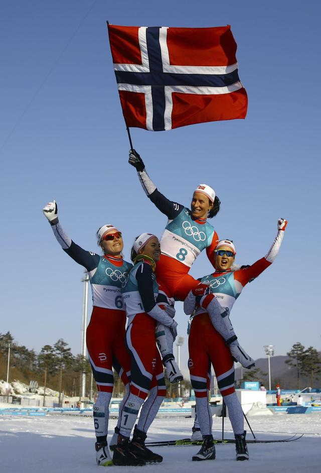 Cross-Country Skiing - Pyeongchang 2018 Winter Olympics - Women's 30km Mass Start Classic - Alpensia Cross-Country Skiing Centre - Pyeongchang, South Korea - February 25, 2018 - Gold medallist Marit Bjoergen of Norway celebrates with compatriots Ingvild Flugstad Oestberg, Heidi Weng and Ragnhild Haga. REUTERS/Carlos Barria