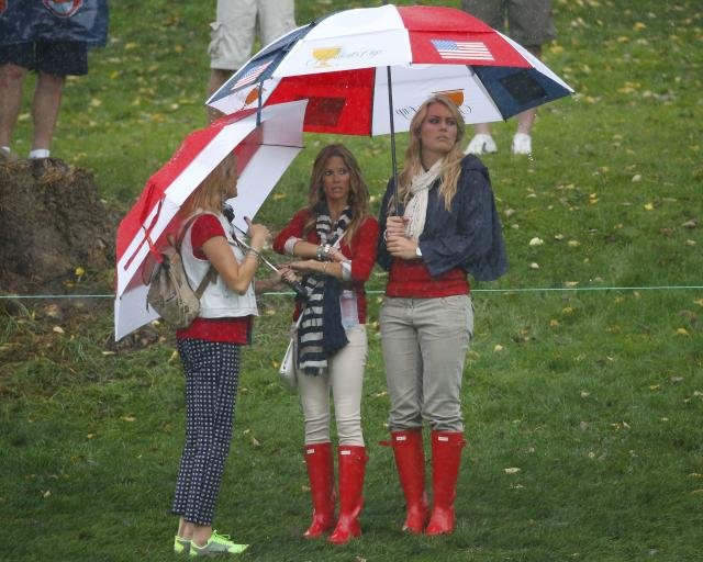 Tiger Woods girlfriend Lindsey Vonn (R) stands under an umbrella with Fred Couples girlfriend Nadine Moze during the Singles matches for the 2013 Presidents Cup golf tournament at Muirfield Village Golf Club in Dublin, Ohio October 6, 2013. REUTERS/Jeff Haynes (UNITED STATES - Tags: SPORT GOLF ENTERTAINMENT)