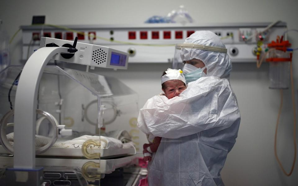 A nurse holds an 11-day-old baby boy infected with Covid-19, at the intensive care unit of the Prof. Dr. Feriha Oz Emergency Hospital - AP Photo/Emrah Gurel