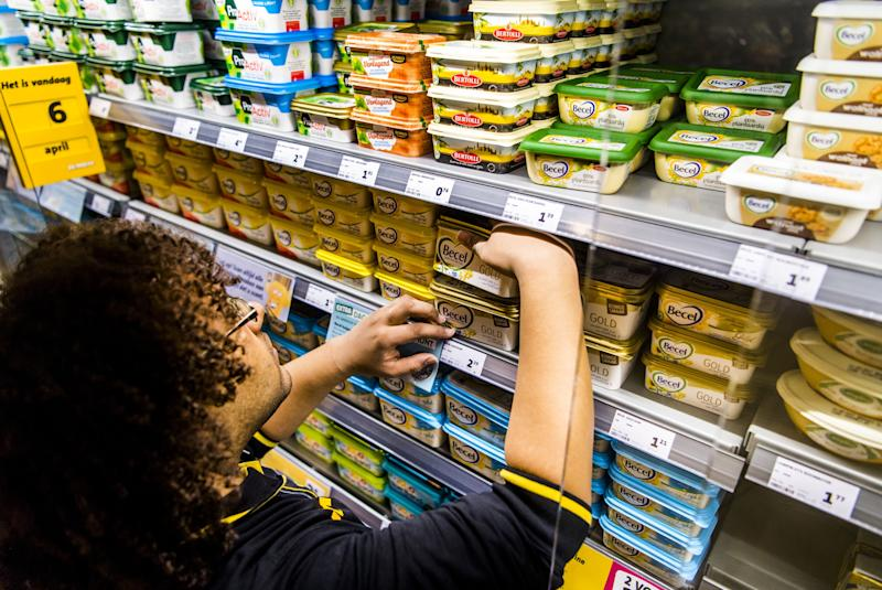 An employee arranges Unilever's margarine brands in a supermarket. Photo: Marco De Swart/AFP/Getty Images