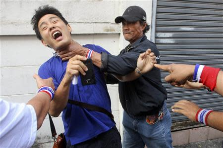 Anti-government protesters attack a voter near a polling station in Bangkok