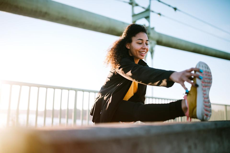 A young mixed race woman stretches before an early jog in the city of Tacoma, Washington. Her running takes her across the Tacoma Narrows bridge, with a running path spanning the Puget Sound from Tacoma to Gig Harbor.