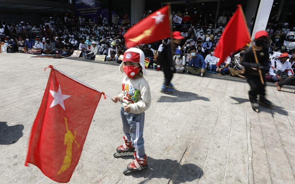 Children hold National League for Democracy (NLD) flags during a protest against the military coup - Shutterstock