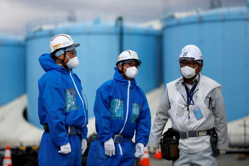 FILE PHOTO: Workers are seen in front of storage tanks for radioactive water are seen at tsunami-crippled Fukushima Daiichi nuclear power plant in Okuma town, Fukushima prefecture