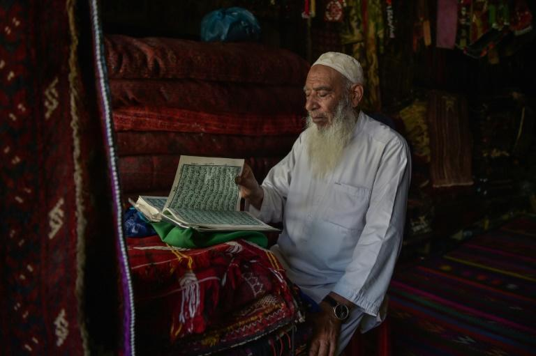 An elderly carpet vendor reads from the holy Quran at his shop in Chicken Street in Kabul (AFP/WAKIL KOHSAR)