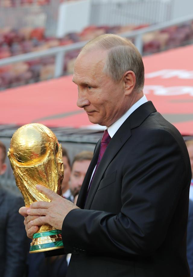 <p>Vladimir Putin with the World Cup trophy (Getty) </p>