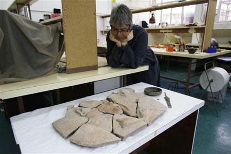 An Israel Antiquities Authority (IAA) employee looks at parts of a broken coffin and other artefacts displayed for the media, at IAA offices in Jerusalem April 9, 2014. REUTERS/Ronen Zvulun