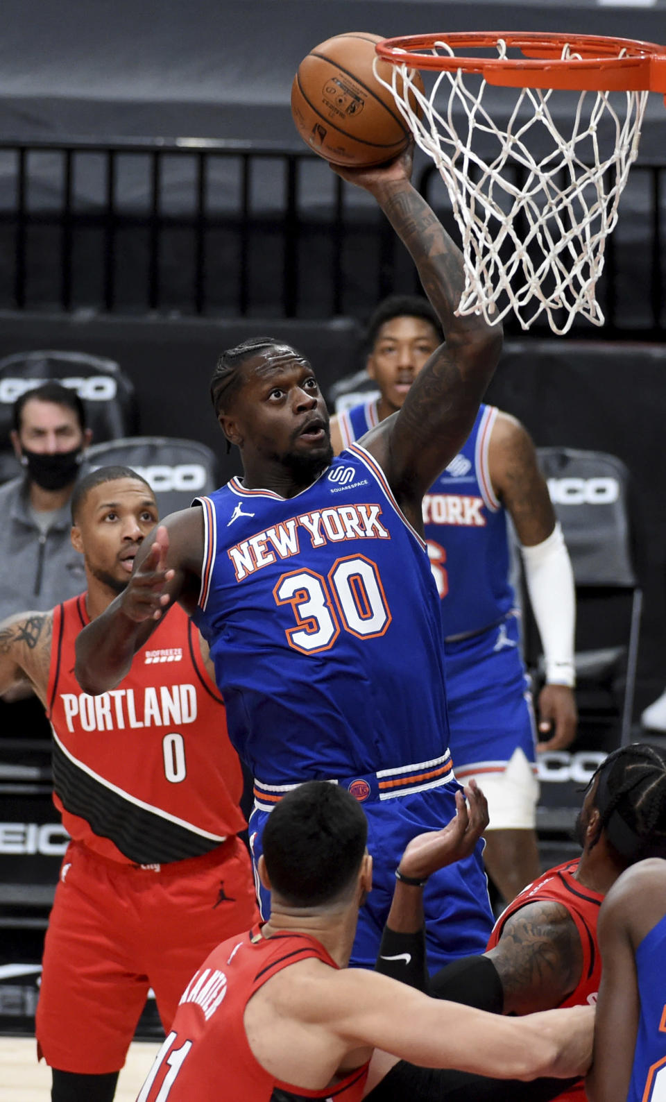 New York Knicks forward Julius Randle (30) drives to the basket on Portland Trail Blazers guard Damian Lillard, left, during the first quarter of an NBA basketball game in Portland, Ore., Sunday, Jan. 24, 2021. (AP Photo/Steve Dykes)