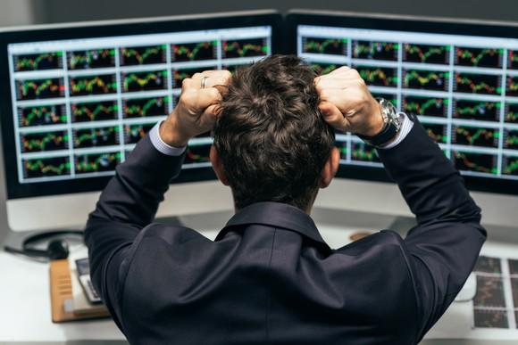 Man in front of monitors displaying stock charts, clenching fists to his head
