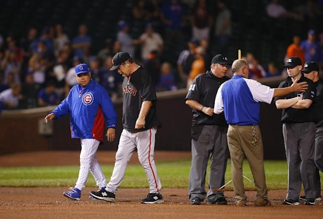 Chicago Cubs manager Rick Renteria and San Francisco Giants manager Bruce Bochy talk with the umpires and officials on the field after a heavy rain soaked Wrigley Field during the fifth inning of a baseball game betwen the San Francisco Giants and the Chicago Cubs on Tuesday, Aug. 19, 2014, in Chicago. (AP Photo/Jeff Haynes)