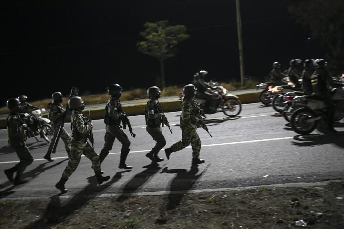 Security forces take part in a military drill to mark the eighth death anniversary of President Hugo Chavez in Caracas, Venezuela, late Friday, March 5, 2021. (AP Photo/Matias Delacroix)