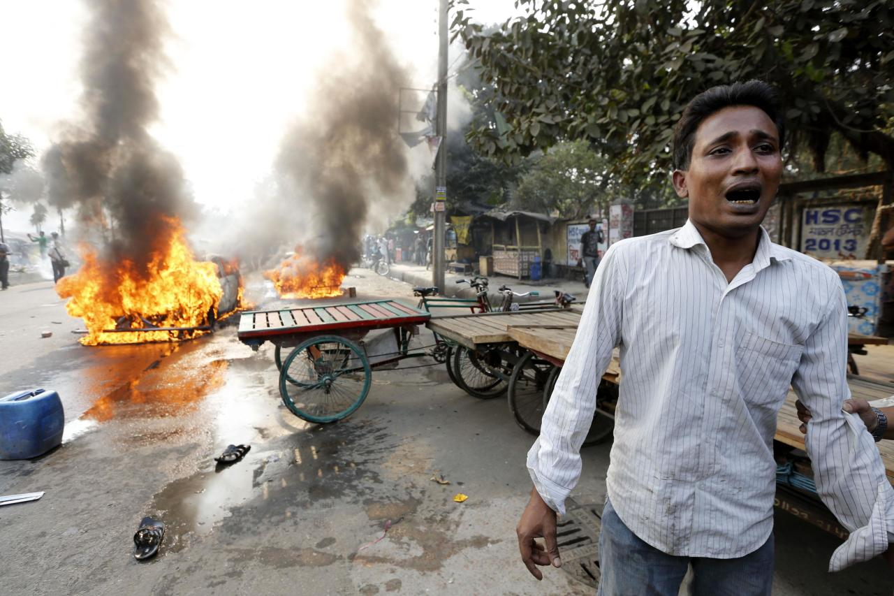 A man cries after Bangladesh's Jamaat-e-Islami party activists torched his vehicle during a clash with police in Dhaka December 13, 2013. At least four people were killed in Bangladesh on Friday when supporters of Islamist leader Abdul Quader Mollah, a senior figure in Jamaat-e-Islami, vented their fury at his execution for war crimes committed during the 1971 war of independence from Pakistan. REUTERS/Andrew Biraj (BANGLADESH - Tags: POLITICS CRIME LAW)