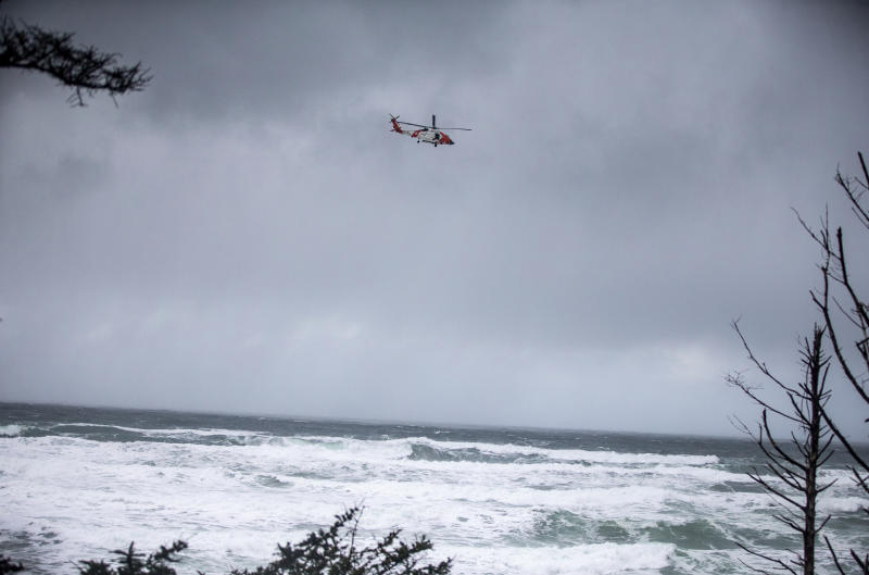 In this Sunday, Jan. 12, 2020 photo, a Coast Guard helicopter continues the search for a missing boy near Falcon Cove Beach in Clastop county, Ore. A 7-year-old girl is dead and her 4-year-old brother is missing after they and their father were swept into the ocean on the Oregon coast amid a high-surf warning. The father was holding the two children when a wave swept all three into the water Saturday, Jan. 11 in the Falcon Cove area, near the small coastal community of Cannon Beach, authorities said.  (Mark Graves/The Oregonian via AP)