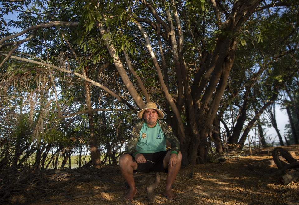 """Fisherman Sandro Branco poses for a photo on teh banks of the Tapajos river in Alter do Chao, district of Santarem, Para state, Brazil, Thursday, Aug. 27, 2020. Dubbed """"the Brazilian Caribbean,"""" Alter do Chao, on the edges of the Tapajos River is facing growing environmental concerns. Real estate development, much of it illegal, flocks of tourists and neighboring ports exporting the country's soybeans and corn are affecting the lives of villagers and of an Indigenous group in the region. (AP Photo/Andre Penner)"""