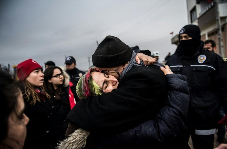 Fevziye Demir hugs her father after a rocket fired from across the border in Syria hit her house in Kilis in Turkey