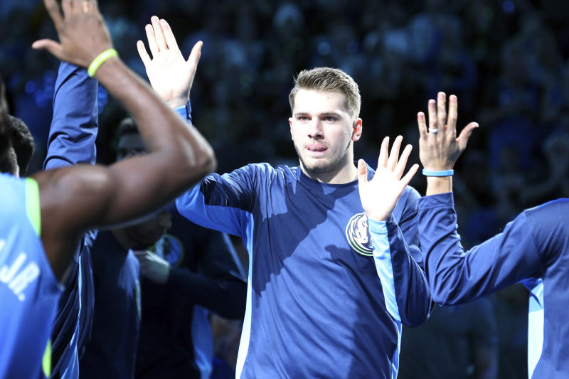 Dallas Mavericks forward Luka Doncic (77) high fives teammates after being introduced before a game against the Sacramento Kings in an NBA basketball game Sunday, Dec. 8, 2019, in Dallas. (AP Photo/Richard W. Rodriguez)