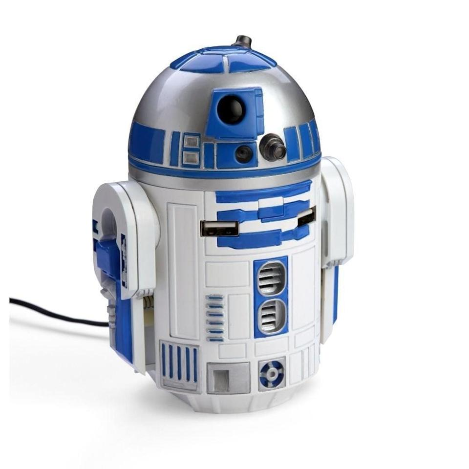 """<p>R2 units are the ultimate helpers, and this <a href=""""https://www.popsugar.com/buy/R2-D2-car-charger-330734?p_name=R2-D2%20car%20charger&retailer=amazon.com&pid=330734&price=65&evar1=geek%3Aus&evar9=36026397&evar98=https%3A%2F%2Fwww.popsugar.com%2Ftech%2Fphoto-gallery%2F36026397%2Fimage%2F36026418%2FR2-D2-Car-Charger&list1=gifts%2Choliday%2Cgift%20guide%2Cdigital%20life%2Cfathers%20day%2Choliday%20living%2Ctech%20gifts%2Cgifts%20for%20men&prop13=mobile&pdata=1"""" class=""""link rapid-noclick-resp"""" rel=""""nofollow noopener"""" target=""""_blank"""" data-ylk=""""slk:R2-D2 car charger"""">R2-D2 car charger</a> ($65) is no exception. The charger sits in a cup holder and plugs into a cigarette lighter. It can charge up to two USB devices at once, and R2's dome even rotates and lights up. When power is connected, the bot will whistle and beep.</p>"""