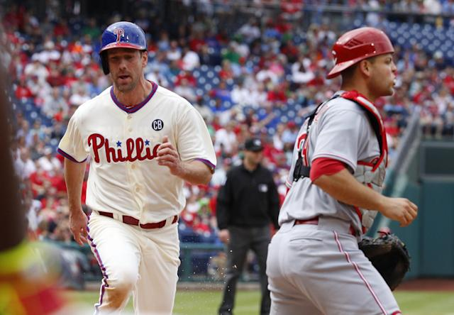 Philadelphia Phillies' Cliff Lee, left, comes in to score on a ground out by Chase Utley as Cincinnati Reds catcher Devin Mesoraco, right, looks for the ball during the fifth inning of a baseball game, Sunday, May 18, 2014, in Philadelphia. (AP Photo/Chris Szagola)