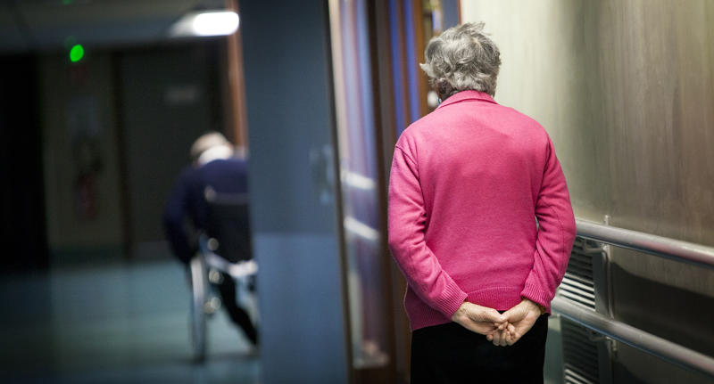 The hallway of an aged care facility with two patients in the halls.