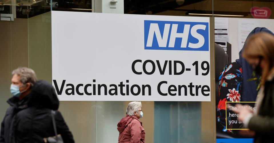 People queue to enter an NHS Covid-19 vaccination centre in Westfield Stratford City shopping centre in east London on February 15, 2021 as Britain's largest ever vaccination programme continues. - Prime Minister Boris Johnson called Britain hitting a target of inoculating 15 million of the most vulnerable people with a first coronavirus jab