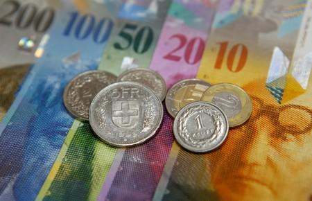 FILE PHOTO: Polish Zloty and Swiss Franc coins lay on top of various Swiss Franc notes in this picture illustration at a bank in Warsaw