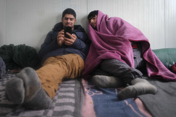 Migrants look at a mobile phone at the Lipa camp, outside Bihac, Bosnia, Monday, Jan. 11, 2021. Aid workers say migrants staying at a camp in northwestern Bosnia have complained or respiratory and skin diseases after spending days in make-shift tents and containers amid freezing weather and snow blizzards. Most of the hundreds of migrants at the Lipa facility near Bosnia's border with Croatia on Monday have been accommodated in heated military tents following days of uncertainty after a fire gutted most of the camp on Dec. 23. (AP Photo/Kemal Softic)