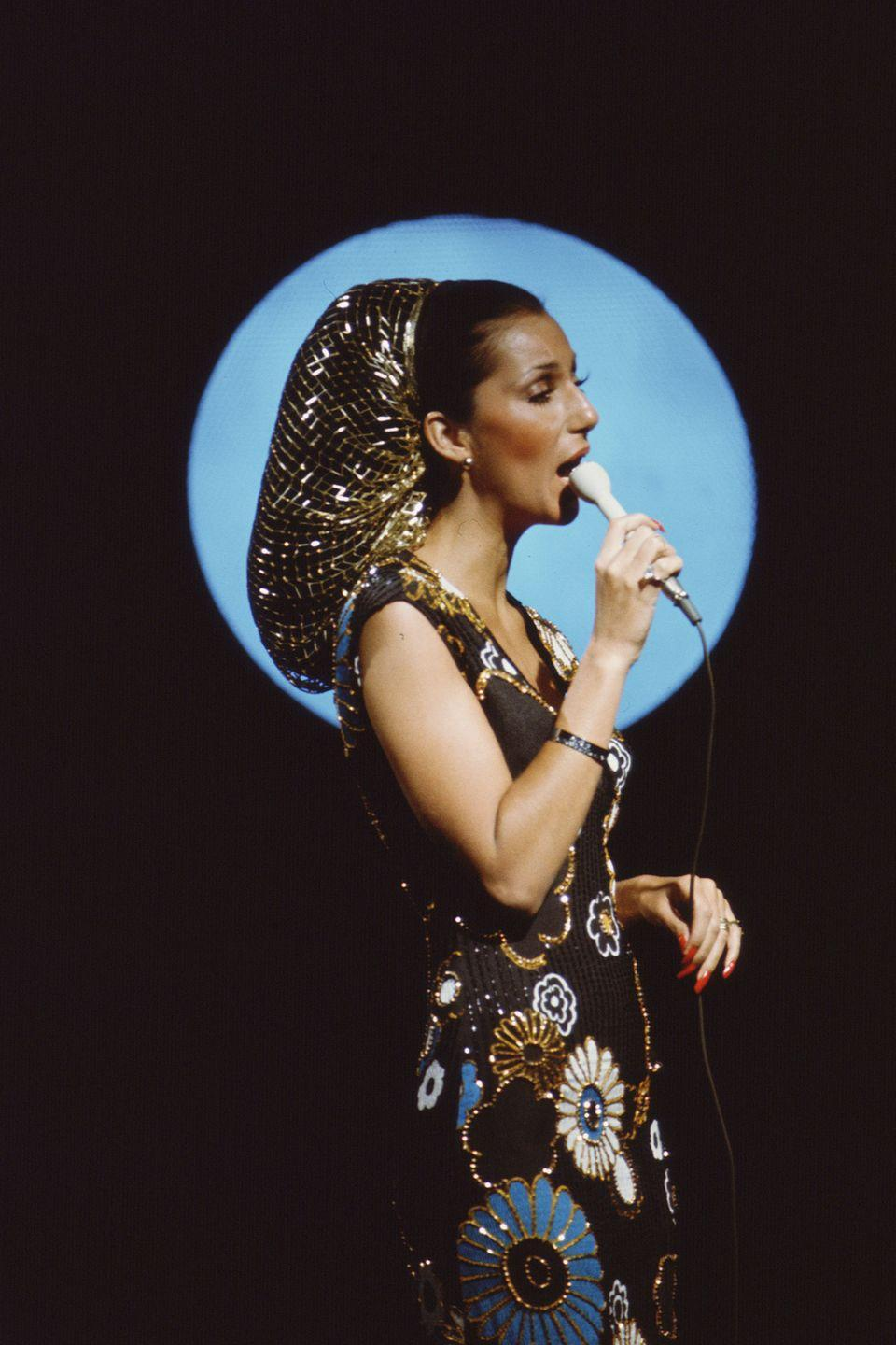 <p>She sings into a microphone for the television variety show <em>The Sonny and Cher Comedy Hour</em>, wearing a bedazzled floral dress and a golden hair net.</p>