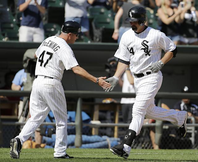 Chicago White Sox's Paul Konerko, right, celebrates with third base coach Joe McEwing after hitting a solo home run during the ninth inning of a baseball game against the Kansas City Royals in Chicago on Saturday, June 14, 2014. The Royals won 9-1. (AP Photo/Nam Y. Huh)
