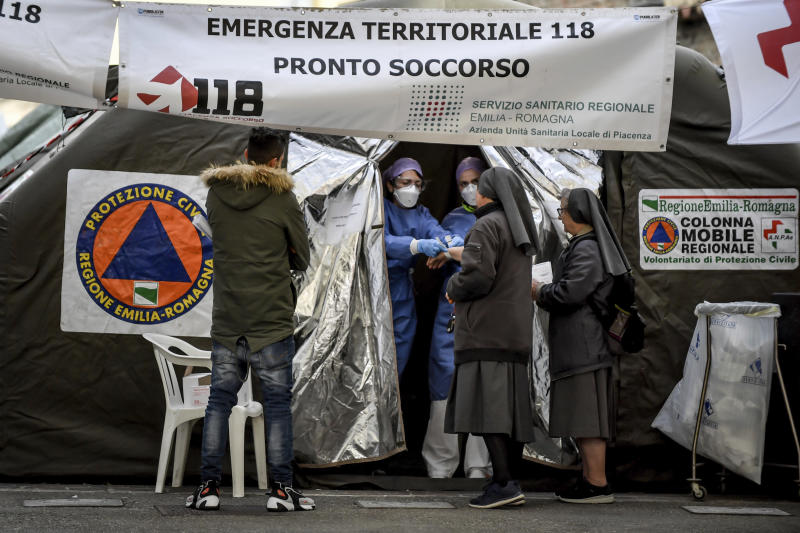 Nuns talks to paramedics at a tent set up by the Italian Civil Protection next to the emergency ward of the Piacenza hospital, northern Italy, Thursday, Feb. 27, 2020. Italy is changing how it reports coronavirus cases and who will get tested in ways that could lower the country's caseload even as an outbreak centered in northern Italy spreads in Europe. (Claudio Furlan/Lapresse via AP)