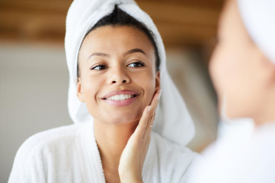 Head and shoulders portrait of  smiling Mixed-Race woman looking in mirror during morning routine, copy space