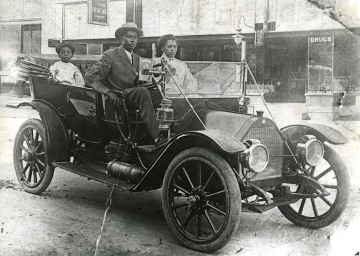 John Wesley Williams and wife, Loula Cotten Williams, and their son, William Danforth Williams, sitting in a 1911 Norwalk automobile. A sign advertising A.L. Black Printing Co. is visible in the background. John was an engineer for Thompson Ice Cream Co. Loula was a teacher. The Williams family owned the Dreamland Theatre, which opened in 1914 and was destroyed in the 1921 Tulsa Race Massacre.