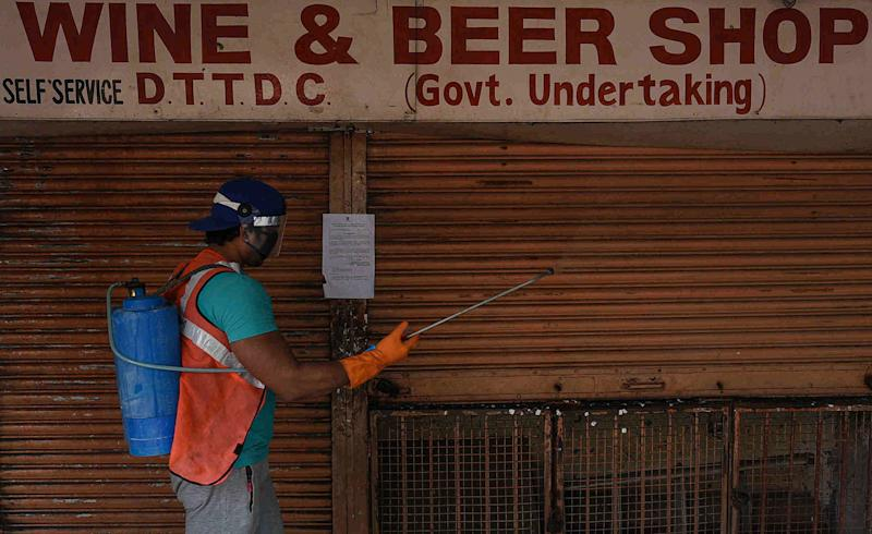 A SDMC worker sanitizes a liquor shop at Vasant Vihar on May 5, 2020 in New Delhi, India. The third phase of the nationwide lockdown began on Monday with considerable relaxations, as the pre-existing quarantine was further extended for the second time by the Ministry of Home Affairs for two weeks beyond May 3. However, governments are also keeping in place necessary curbs so as to not lose all the gains that have been achieved in the battle against the virus. The total number of cases stood at 46,433 which includes 32,138 active cases, 12,726 recovered cases, 1 migrant patient and 1,568 deaths as per Ministry of Health data at 9 am IST on Tuesday. (Photo by Biplov Bhuyan/Hindustan Times via Getty Images)