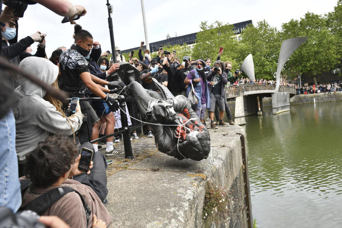 Protesters throw a statue of slave trader Edward Colston into Bristol harbour during a Black Lives Matter protest rally. (AP)